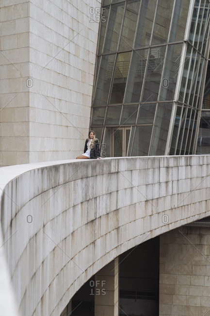 Female entrepreneur sitting on retaining wall of office building