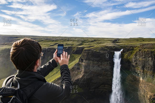 Tourist taking photo of Haifoss waterfall through mobile phone while standing at Iceland