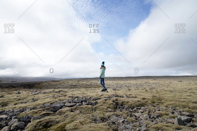 Girl looking away while standing against sky