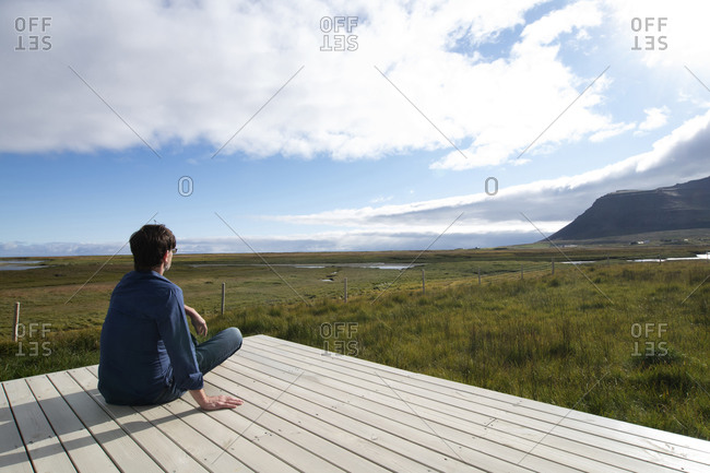 Man looking at view while sitting on terrace at Flokalundur- Iceland