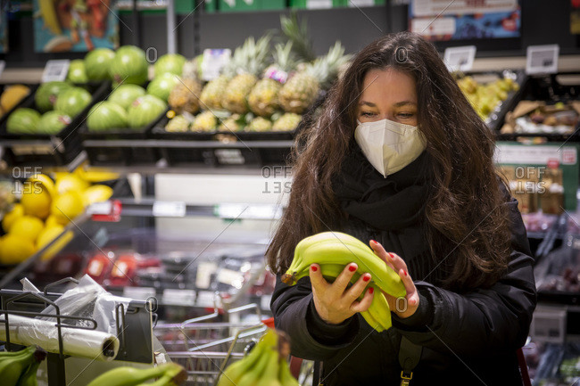 Mature woman buying bananas while grocery shopping during COVID-19