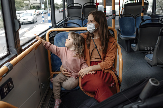 Mother with cute daughter pointing at window while traveling by bus during COVID-19