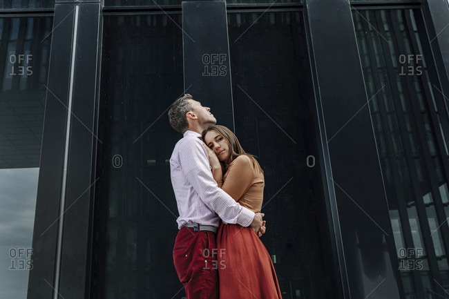 Affectionate heterosexual couple embracing against building