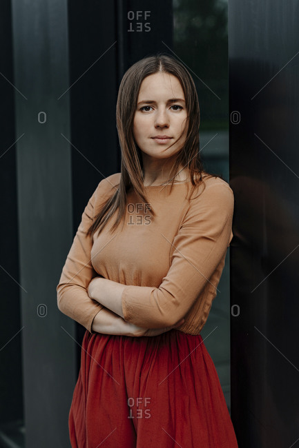 Confident woman with arms crossed against building