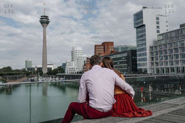 Heterosexual couple embracing while sitting on bridge in city