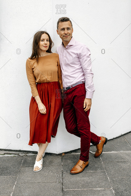 Smiling heterosexual couple against white wall