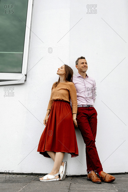 Heterosexual couple against white wall
