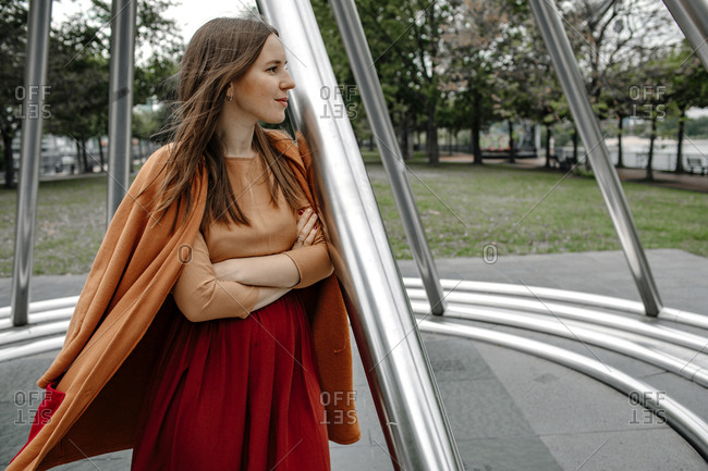 Woman day dreaming while leaning on metal pole in public park