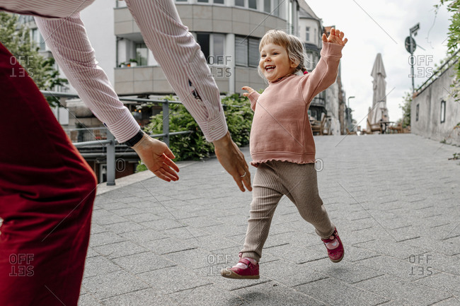 Cheerful daughter running towards her father while playing on street in city