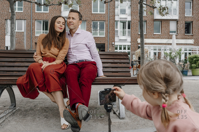 Daughter taking photograph of parents through mobile phone while sitting on park bench