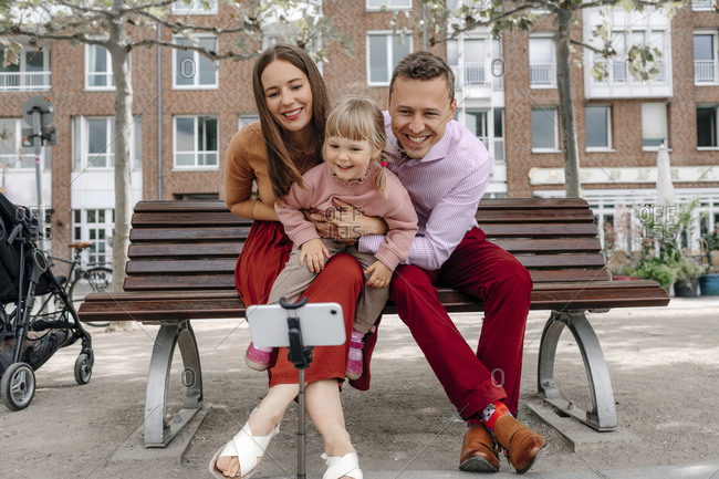 Happy family with one daughter talking selfie from mobile phone on tripod at park bench