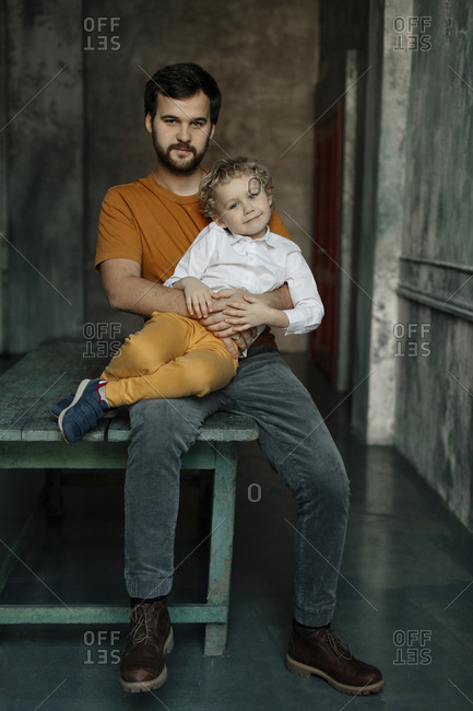 Father holding son while sitting on bench