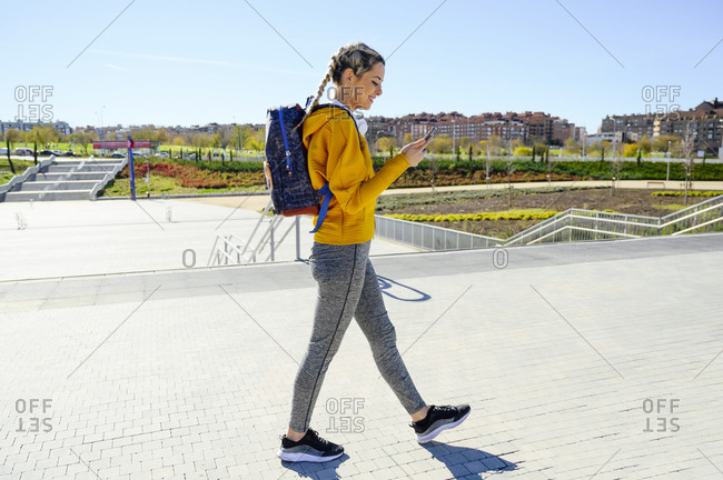 Female athlete with backpack using mobile phone while walking on footpath