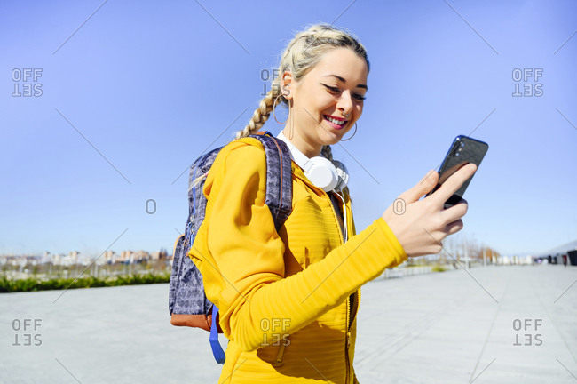Smiling sportswoman using mobile phone while standing against clear sky