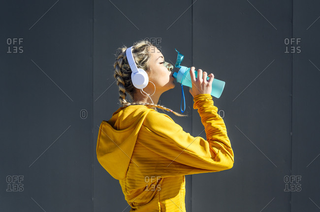 Sportswoman wearing headphones drinking water while standing against gray wall