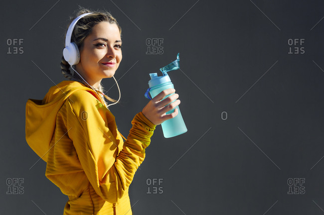 Smiling sportswoman wearing headphones holding water bottle while standing against gray wall
