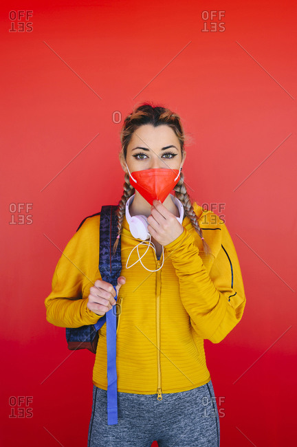 Sportswoman with backpack adjusting face mask while standing against red wall