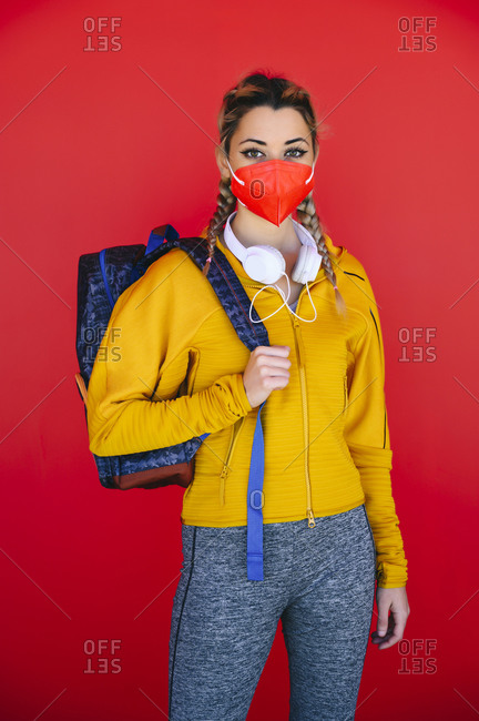 Athlete wearing face mask carrying backpack while standing against red wall