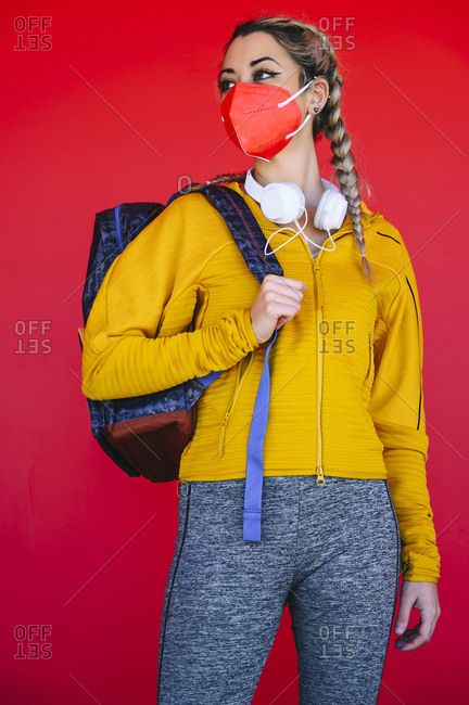 Female athlete wearing face mask looking away while standing against red wall