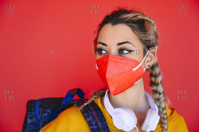 Young sportswoman wearing protective face mask looking away while standing against red wall