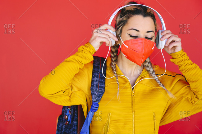 Sportswoman with protective face mask wearing headphones while standing against red wall