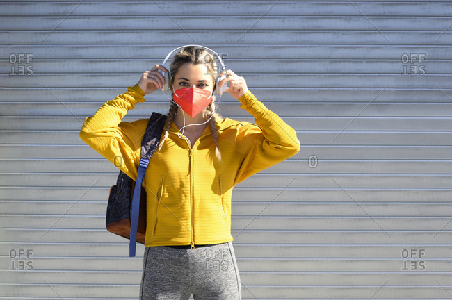 Female athlete with protective face mask wearing headphones while standing against shutter