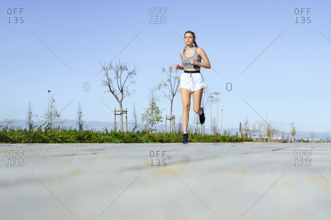 Young athlete running on footpath against sky