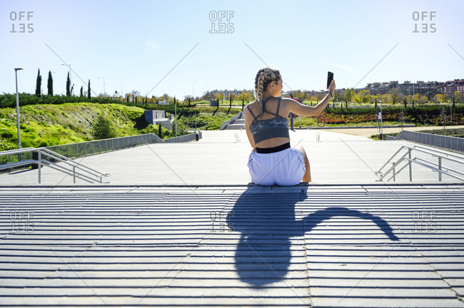 Sportswoman taking selfie through mobile phone while sitting on footpath during sunny day