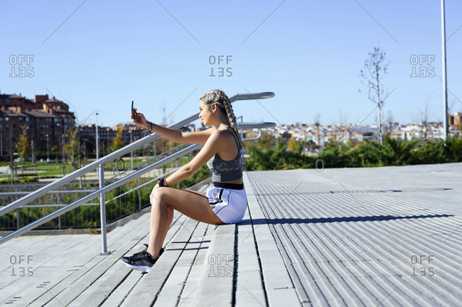 Young sportswoman taking selfie while sitting on staircase during sunny day