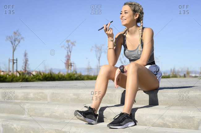 Smiling sportswoman talking on mobile phone while sitting on steps