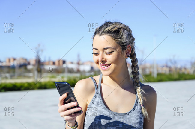 Sportswoman smiling while using mobile phone standing on footpath