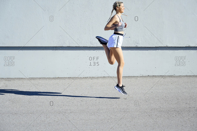 Young sportswoman running against wall during sunny day
