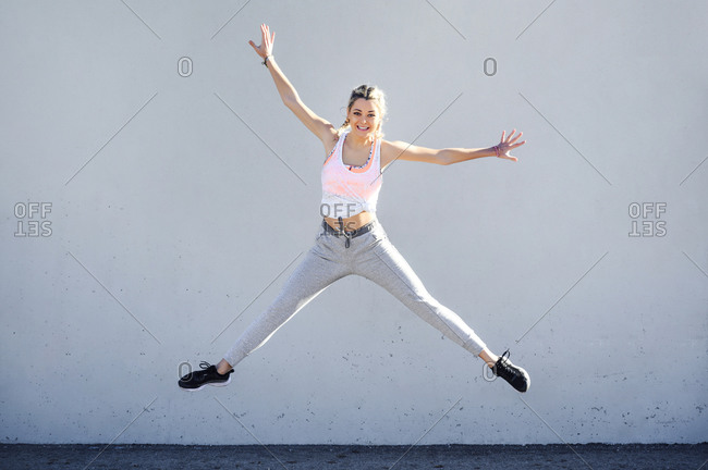 Carefree sportswoman jumping with arms outstretched against wall