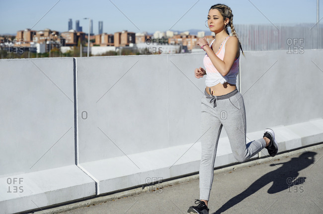 Athlete running by retaining wall during sunny day