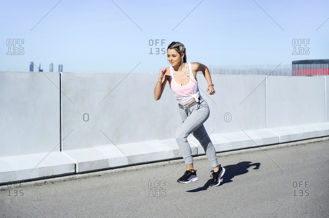 Young female athlete exercising while running on footpath during sunny day