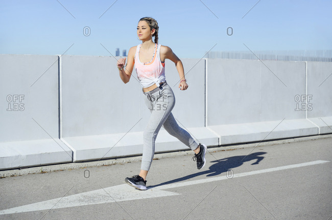 Sportswoman practicing while running on footpath