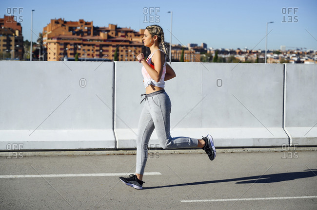 Young sportswoman running on footpath during sunny day