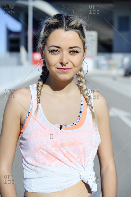 Confident sportswoman staring while standing outdoors