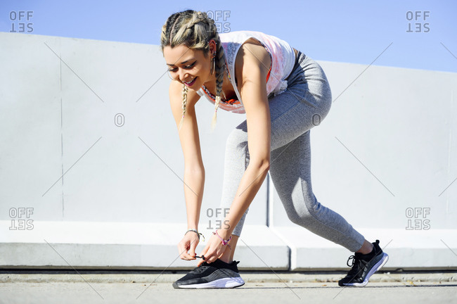 Smiling athlete tying shoelace while standing against retaining wall