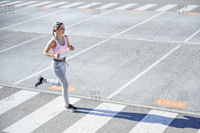 Smiling sportswoman exercising while running on road