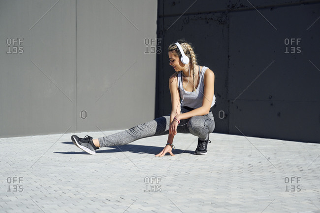 Young athlete wearing headphones stretching while crouching on footpath