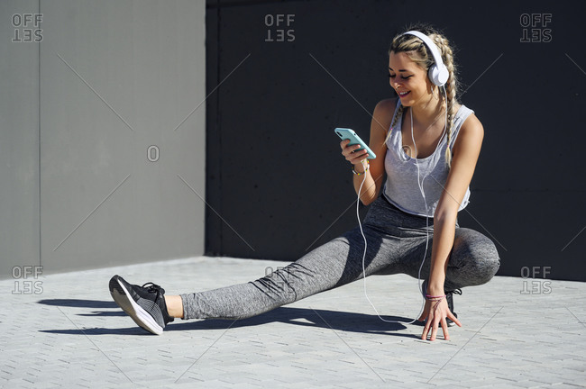 Smiling sportswoman wearing headphones using mobile phone while crouching on footpath