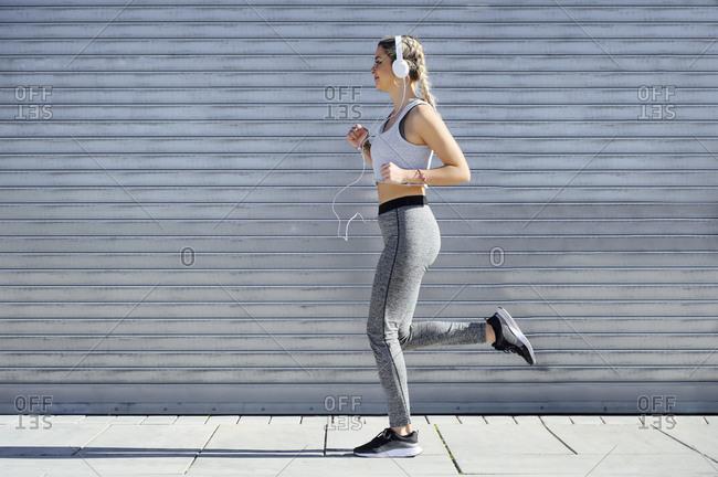 Female athlete wearing headphones jogging against shutter