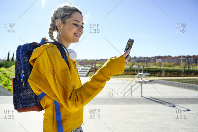 Smiling sportswoman with backpack using mobile phone while standing on footpath