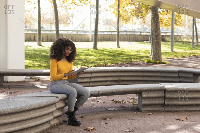 Afro woman using digital tablet while sitting on stone bench in public park