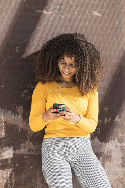 Fashionable young woman using mobile phone while leaning on wall