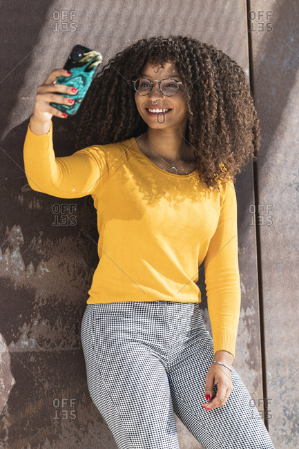 Smiling young woman with curly hair taking selfie against wall