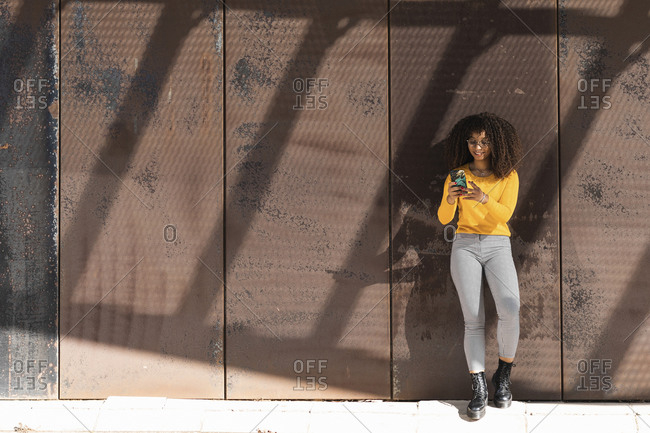Fashionable woman in yellow sweater using mobile phone against wall on sunny day