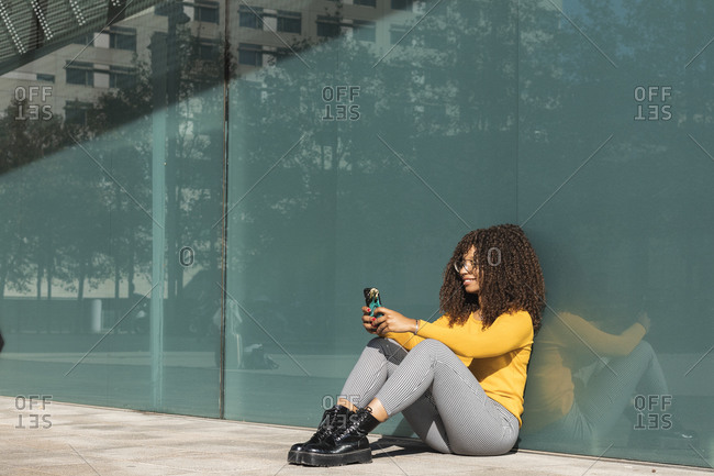 Smiling young woman using mobile phone while leaning on glass during sunny day