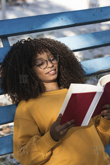 Smiling young woman reading book while lying on blue bleachers